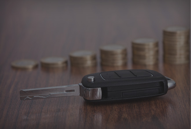 car key and stacked coins on a table